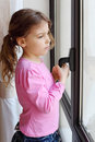 Girl stands near window and holds handle of frame Royalty Free Stock Images