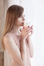 Girl stands at the window with a mug Royalty Free Stock Photo