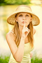 Girl in straw hat calls for silence Royalty Free Stock Photo
