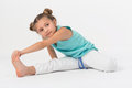 A girl stretches hand and makes gymnastic exercise to leg Royalty Free Stock Image