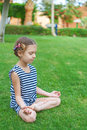 Girl in striped vest sits in lotus position little on green lawn Stock Photo