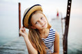 Girl in striped vest and a straw hat against the sea Royalty Free Stock Photo