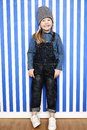 Girl in stripy hat grinning young striped and dungarees Stock Photography