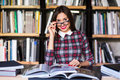 Girl student with glasses reading books in the library Royalty Free Stock Photo
