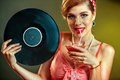 Girl in style keeps vinyl record and drink martini cocktail . Royalty Free Stock Photo
