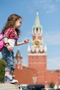 Girl in stylish dress and sunglasses near the kremlin little with a compass hand stands profile Royalty Free Stock Image
