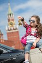 Girl in stylish dress and sunglasses near the kremlin little with a compass hand toy box with inscription russia Stock Photo