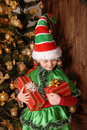 Girl in suit of christmas elf with a gift the near xmas fir tree Stock Image