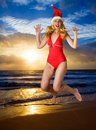 The girl in a suit of Santa Claus jumps on an ocea Royalty Free Stock Photography