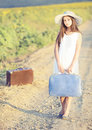 Girl with suitcase on a country road Stock Photos