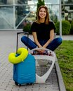 A girl with a suitcase and travel pillow on the bench near the airport is waiting for flight Royalty Free Stock Photo