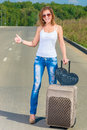 Girl with a suitcase traveling hitchhike on the road Royalty Free Stock Photos