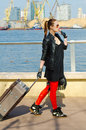 Girl with a suitcase walking along the waterfront Royalty Free Stock Photo