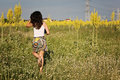 Girl summer outfit walking in the field yellow flowers Stock Images