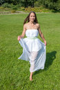 Girl in summer park beautiful white dress enjoying green Royalty Free Stock Photo