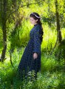 Girl on a summer sunny day walking and dancing in the forest wit Royalty Free Stock Photo