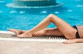 The girl sunbathes near the pool Royalty Free Stock Image
