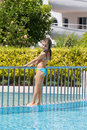 The girl sunbathes standing on edge of pool holding handrails Stock Photos