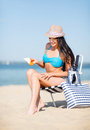 Girl sunbathing on the beach chair summer holidays and vacation applying sun protection cream Royalty Free Stock Images