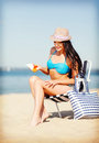 Girl sunbathing on the beach chair summer holidays and vacation applying sun protection cream Stock Photography