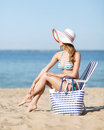 Girl sunbathing on the beach chair summer holidays and vacation putting sun protection cream Stock Images