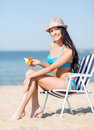 Girl sunbathing on the beach chair summer holidays and vacation putting sun protection cream Royalty Free Stock Photography