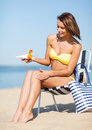 Girl sunbathing on the beach chair summer holidays and vacation putting sun protection cream Royalty Free Stock Images