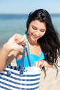 Girl sunbathing on the beach summer holidays vacation and concept in bikini with bag Royalty Free Stock Photography
