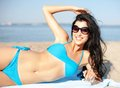 Girl sunbathing on the beach summer holidays vacation and concept in shades Stock Images