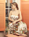 Girl in sundress sitting and looking out window Royalty Free Stock Photo