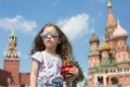 Girl in sunglasses and jeans with suspenders with miniature cathedral little a near the kremlin Royalty Free Stock Photo