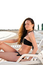 Girl suntanning sexy at the beach sitting on a lounge chair sunny day of summer Royalty Free Stock Photo