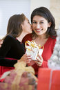 Girl Surprising Her Mother With Christmas Gift Stock Images