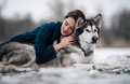 Girl in sweater lies and hugs dog Alaskan Malamute Royalty Free Stock Photo