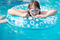 Girl in swim goggle on inflatable circle blue open air pool Stock Photography