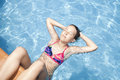Girl in the swimming pool in the very sunny day Stock Images