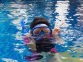 Girl swimming wearing goggles relaxing on the side of a pool and snorkel Stock Photography