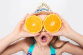 Girl in swimsuit making fake eyeglasses with oranges Royalty Free Stock Photo