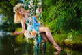 Girl on swing over river Royalty Free Stock Photo