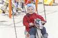 Girl on swing in park smiling Royalty Free Stock Image