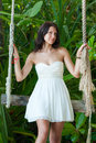 Girl on the swing in the tropics beautiful young white dress is swinging rope Stock Photos