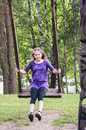 Girl swinging on a wooden swing Royalty Free Stock Photography