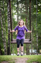 Girl swinging on a wooden swing Royalty Free Stock Photo