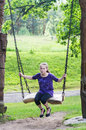Girl swinging on a wooden swing Stock Photo