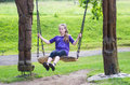 Girl swinging on a wooden swing Stock Image