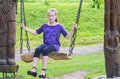 Girl swinging on a wooden swing Royalty Free Stock Photos