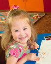 Girl syndrome down syndrome the child draws and smiling Stock Image