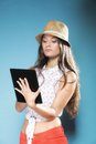 Girl with tablet computer ebook reader touchpad pc internet modern lifestyle concept young summer in hat using reading latin Royalty Free Stock Image