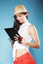 Girl with tablet computer ebook reader touchpad pc internet modern lifestyle concept young summer in hat using reading latin Royalty Free Stock Photo