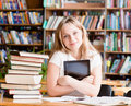 Girl with tablet computer in library Royalty Free Stock Photo